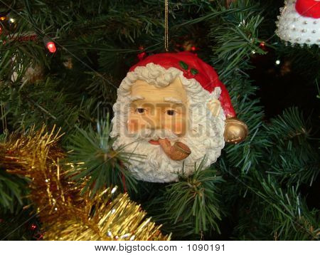 Picture or Photo of Santa claus ornament hanging on tree with gold garland and tree in background.