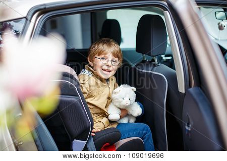 Portrait of preschool kid boy sitting in car
