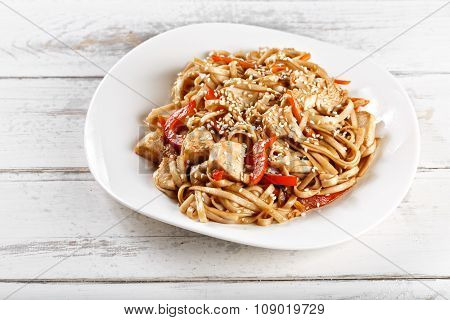 fried noodles udon with chicken on wooden table