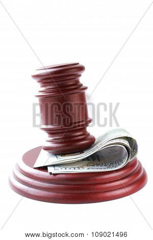 gavel on a stand with money (US dollars) on a white background