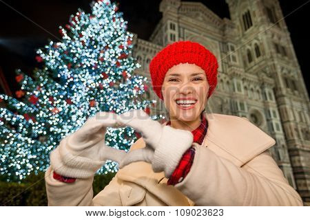 Woman Showing Heart Shaped Hands Near Christmas Tree In Florence