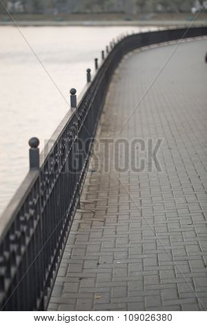 Paved walk, cast iron fence down the river bank