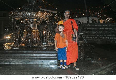 Buddhist Monk Holds A Westerner Cute Boy In His Hand