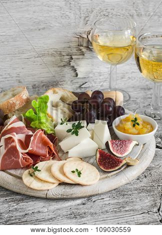 Ham, Cheese, Grapes, Figs, Nuts, Bread Ciabatta, Cracker, Jam On White Wooden Board And Two Glasses