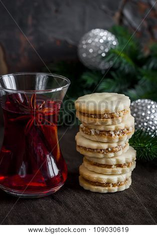 Tea With Spices And Herbs And Shortbread Biscuits With Caramel Cream And Walnuts On A Dark Surface