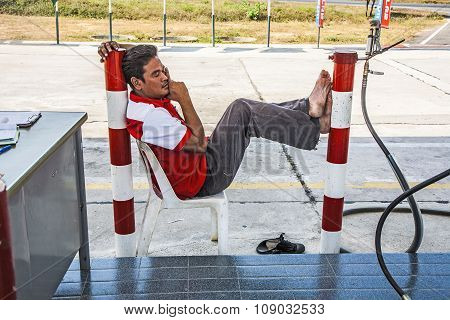 Worker At The Petrol Station Sleeping On A Plastic Chair