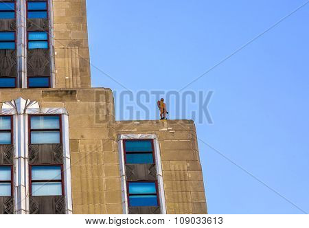 Facade Of Skyscraper With Statue Of Man