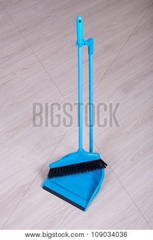 Scoop And Broom Over Wooden Floor Background