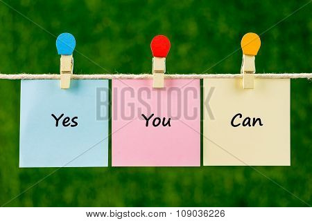 Words Of Yes You Can On Sticky Color Papers Hanging By A Rope.