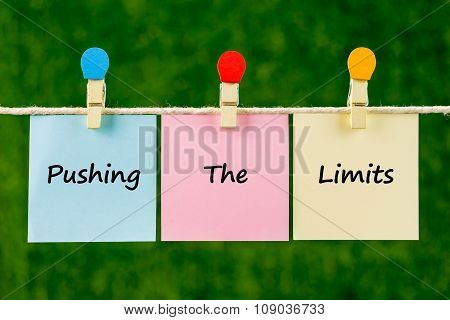 Words Of Pushing The Limits On Sticky Color Papers Hanging By A Rope.