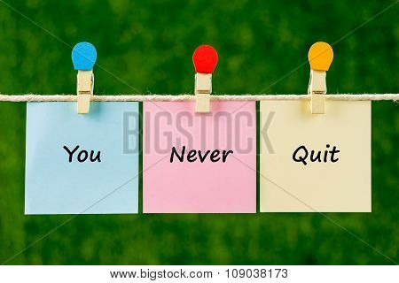 Word Quotes Of You Never Quit On Sticky Color Papers Hanging On Rope.