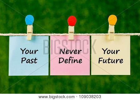 Word Quotes Of Your Past Never Define Your Future On Sticky Color Papers Hanging On Rope.