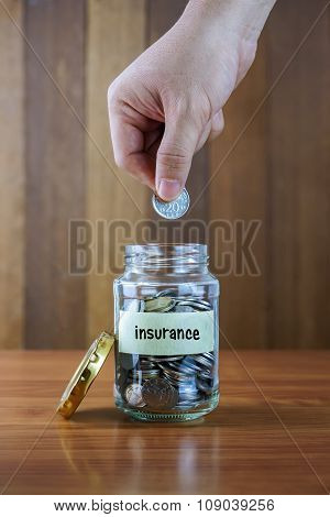 Image Of Hands Putting Coin Into Clear Bottle With Insurance Label Against Blurred Wooden Background