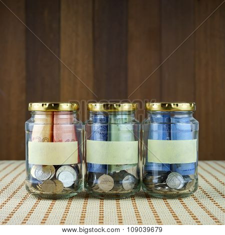 Image Of Money In Three Clear Bottles With Blank Labels.