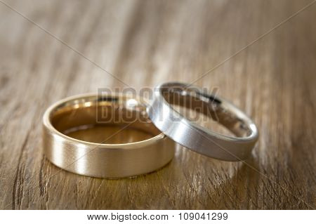 Two wedding rings on a wooden surface