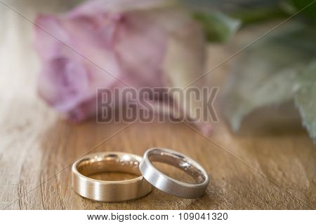 Two wedding rings on a wooden surface with rose