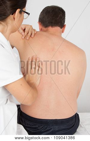 Physiotherapist Stretching A Man Back In Medical Office