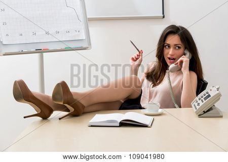 Business woman with her legs on the table.