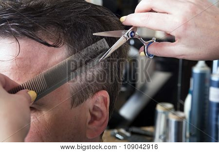Barber cuts hair of handsome satisfied client.