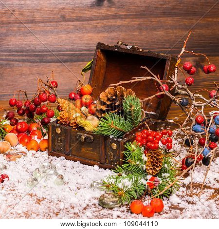 Christmas Winter Still Life With Opened Full Chest, Apple, Nuts, Cones, Berries, Fir Tree And Snow,