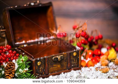 Christmas Winter Concept With Opened Chest, Apple, Nuts, Cones, Berries, Fir Tree And Snow, Closeup