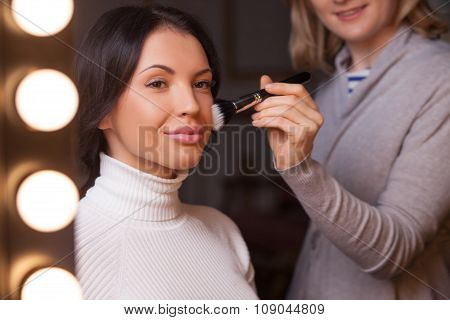 Experienced female visagiste is making the lady beautiful
