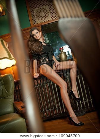 Young beautiful brunette woman in black tight fit body posing sensual in vintage scenery. Romantic