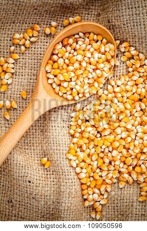 Grains Of Ripe Corn In The Wooden Spoon With Dried Sweet Corn On Hemp Sacks Background .