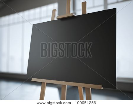 Wooden easel with a blank black canvas in modern interior.