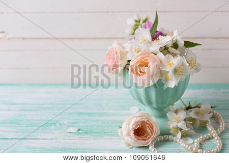 Pastel  Roses And Jasmine Flowers  In Vase On Turquoise Wooden Background.