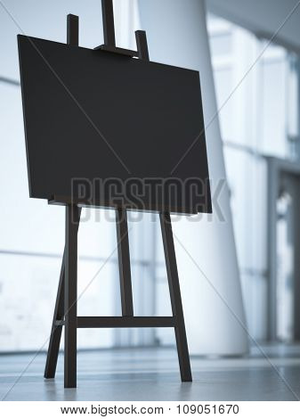 Wooden easel with a blank white canvas in office interior.
