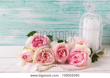 Background With  Pink Roses Flowers, Pearl And Candle  In Decorative Bird Cage