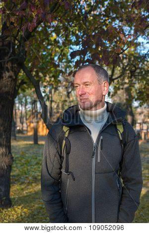 Attractive Man With Backpack Relaxing In Autumn Park