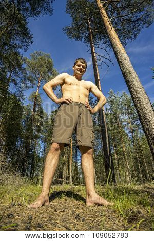 Young Man Stands In The Woods Legs Wide Apart.