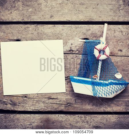 Decorative Sailing Boat And Empty Tag On  Vintage Wooden Background.