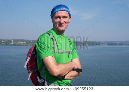 Hiker Man With A Backpack Laughing, Looking At Camera On The Background Of A Wide Big River