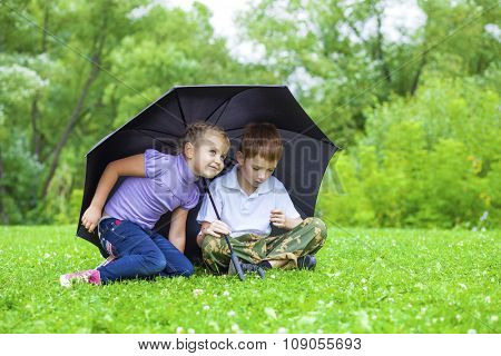 Little girl and boy with black umbrella playing in the summer park