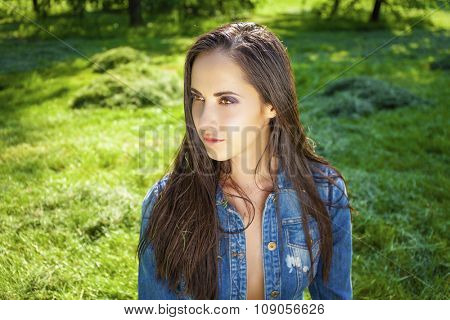 Beautiful young brunette woman in blue jeans jacket in summer park