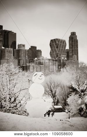 Snowman in Central Park winter with skyscrapers in midtown Manhattan New York City