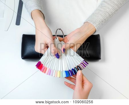Girl look dark palette of varnish for nail polish