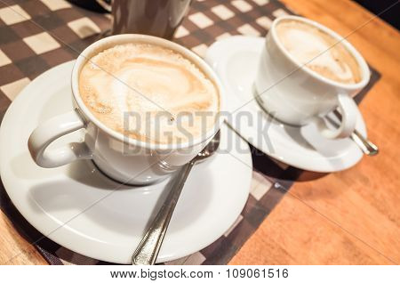 White Cups Full Of Cappuccino Stand On Wooden Table