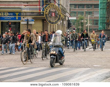 Amsterdam, Netherlands - October 19, 2006: People Riding Bicycles On Central Street In Historical Pa