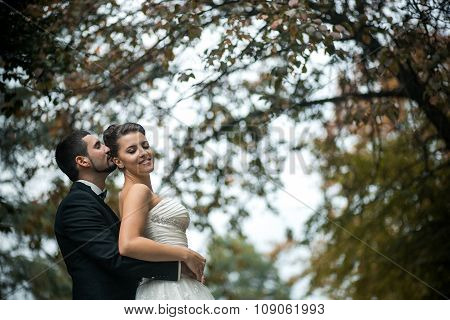 groom embracing bride from back