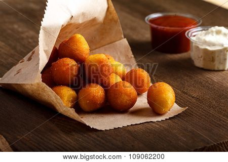 potato croquettes with red and white sauce on wooden table