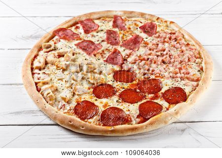 Delicious 4 In 1 Fresh Pizza With Different Kinds Of Meat Served On Wooden Table