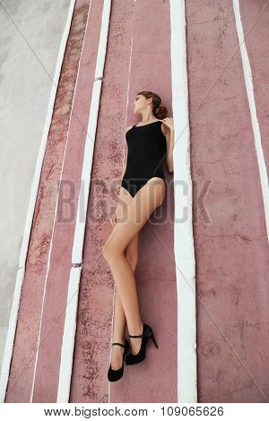 Beautiful Young Girl With Dark Hair In Elegant Swimsuit Lying On Floor