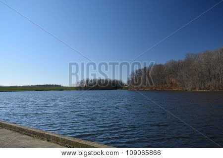 the view across a lake looking at a earthen dam