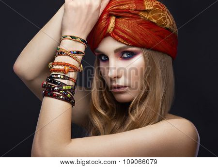 Beautiful fashion girl in a scarf and bracelets boho style. Beauty face, bright trendy makeup.