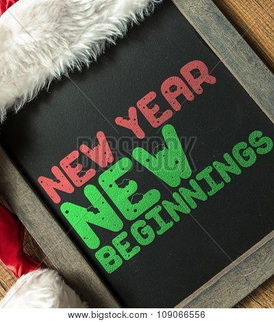 New Year New Beginnings written on blackboard with santa hat