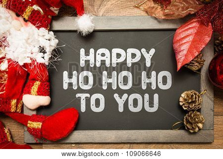 Blackboard with the text: Happy Ho Ho Ho To You in a christmas conceptual image